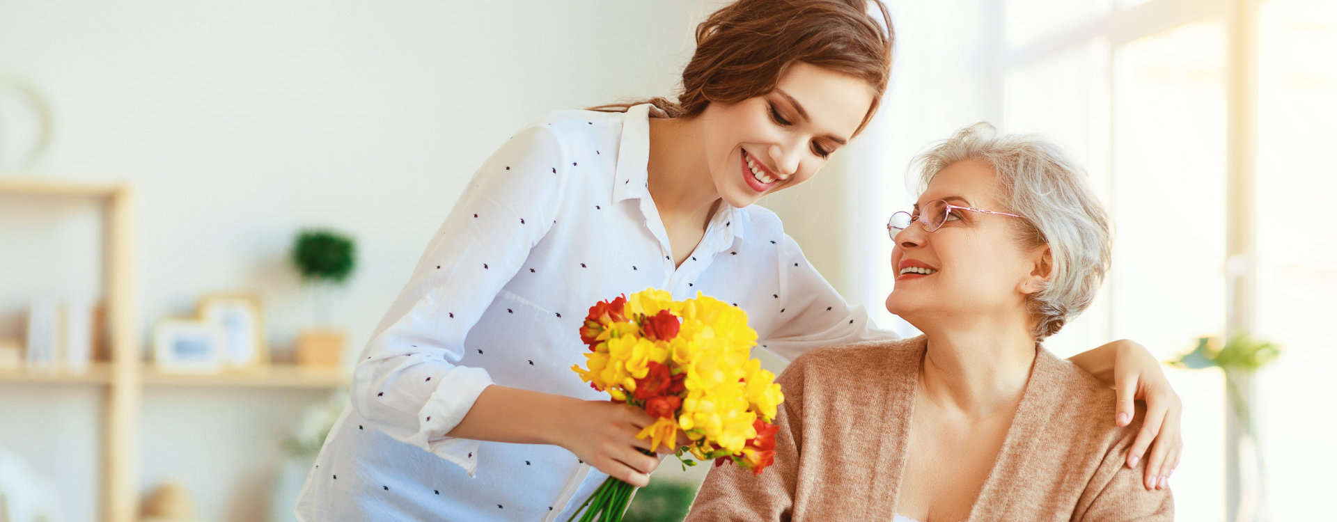 lady gives flower to elder woman