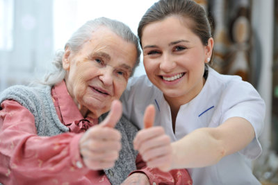 senior woman and her caregiver smiling