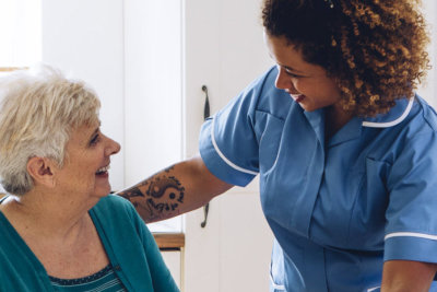 caregiver and senior woman looking at each other while smiling